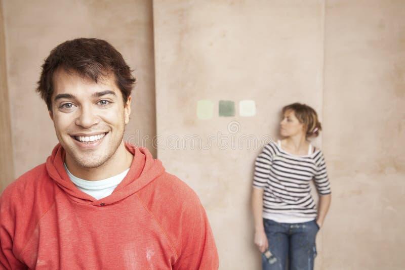 有看在墙壁上的妇女的愉快的人颜色样品 免版税库存照片