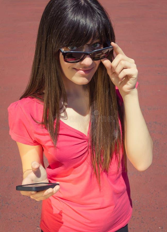 有看在她的太阳镜的电话的少妇 图库摄影