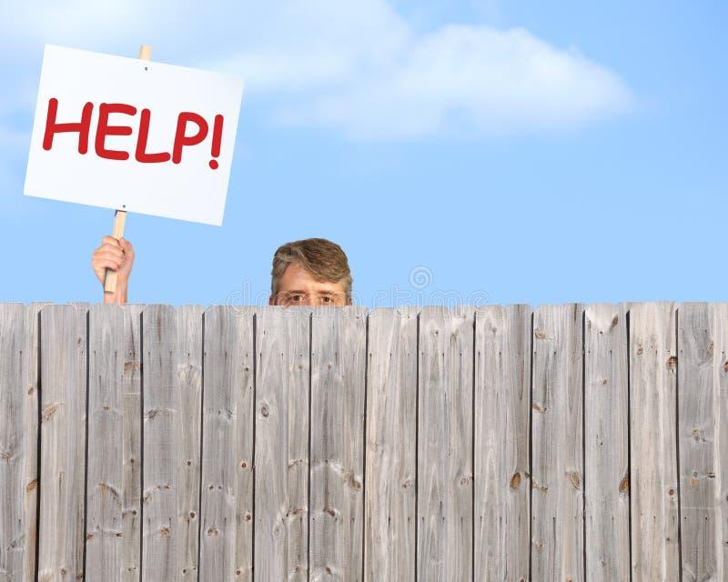 有看在木保密性篱芭的帮助标志的人 免版税库存照片