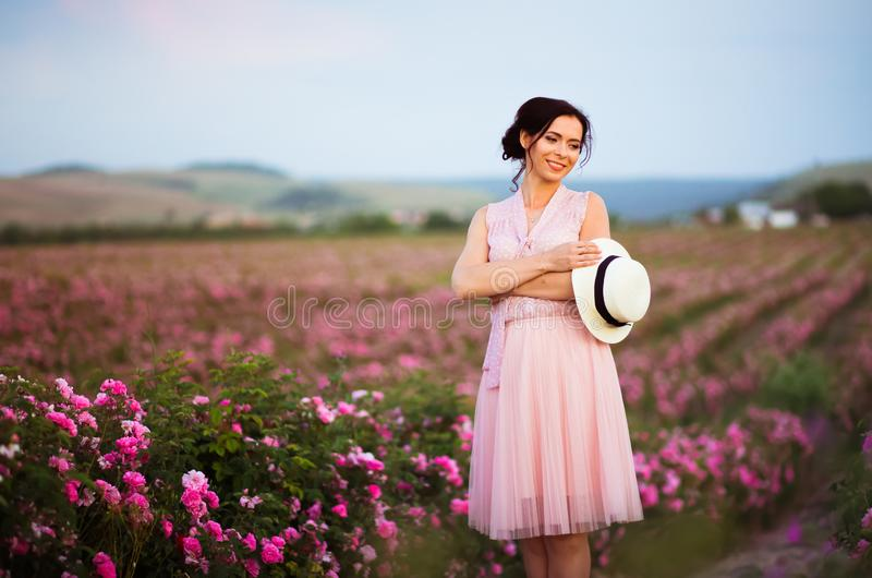 有看在玫瑰的草帽的美丽的年轻女人日落调遣 芳香、化妆用品和香水广告 库存图片
