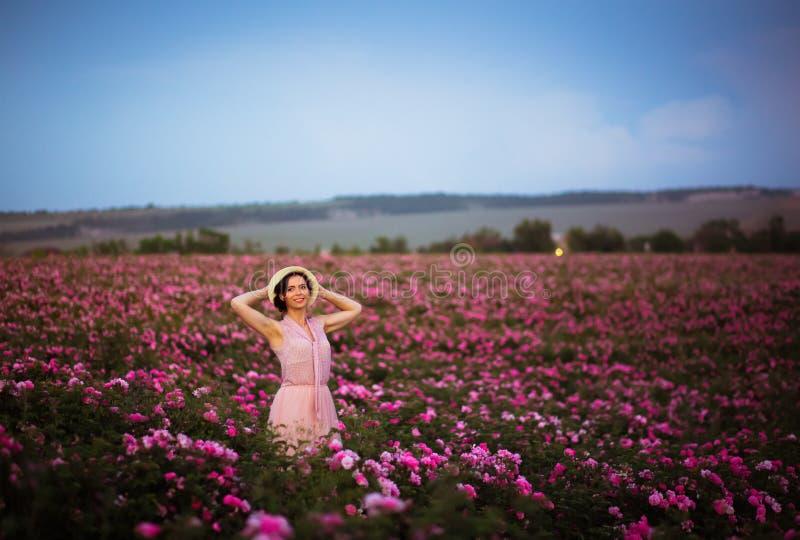 有看在玫瑰的草帽的美丽的年轻女人日落调遣 芳香、化妆用品和香水广告 免版税图库摄影