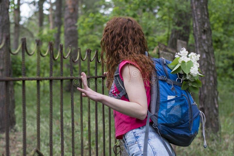 有看在篱芭的背包的美丽的红色头发妇女 库存照片