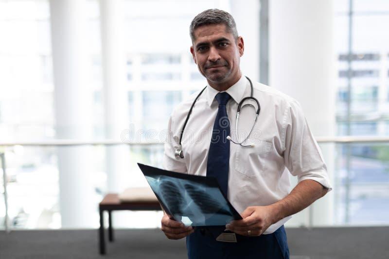 有看在诊所的X-射线的白种人男性医生照相机 免版税图库摄影