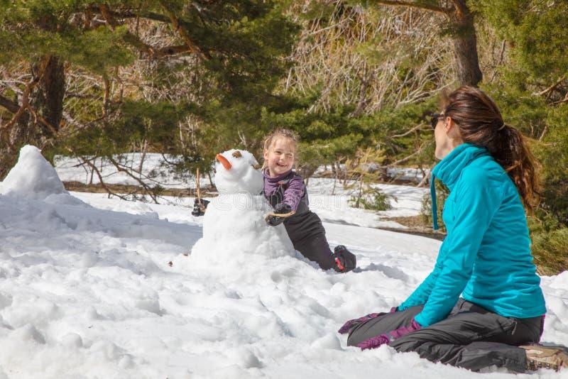 有看她的母亲的雪人的微笑的小女孩 库存图片
