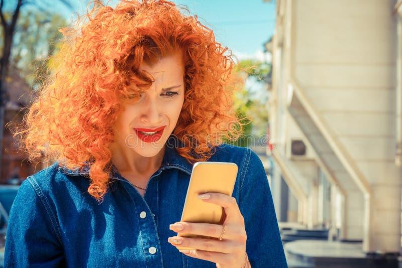 有看对手机的红色卷发的沮丧的恼怒的妇女 免版税库存照片
