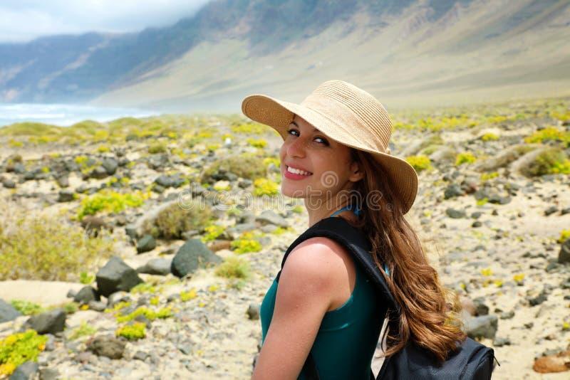 有看对照相机的草帽的愉快的美丽的旅客女孩 探索兰萨罗特岛,加那利群岛的年轻女性背包徒步旅行者 免版税图库摄影