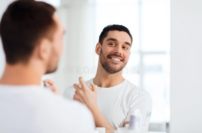 有看对镜子的香水的人卫生间 免版税库存照片