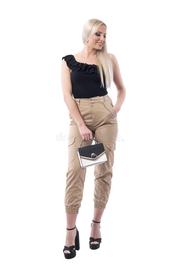 有看小的提包的愉快的微笑的典雅的迷人的年轻白肤金发的妇女下来 免版税库存图片