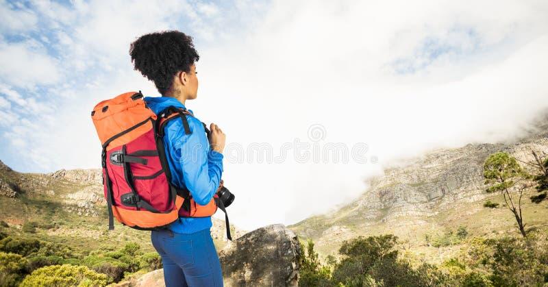 有看山的照相机的行家运载的背包,当站立在峭壁反对天空时 库存图片