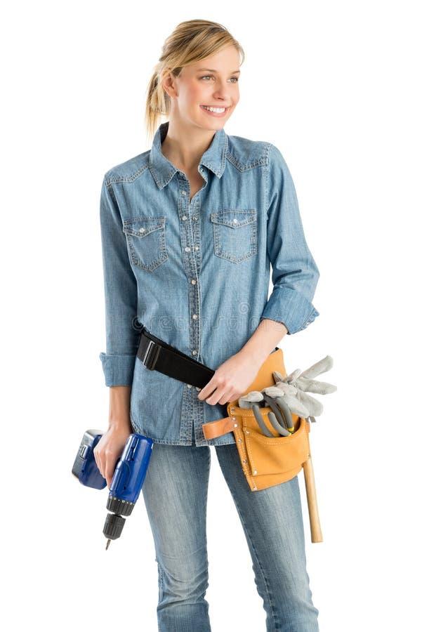 有看工具的传送带和的钻子的女性建筑工人  免版税库存图片