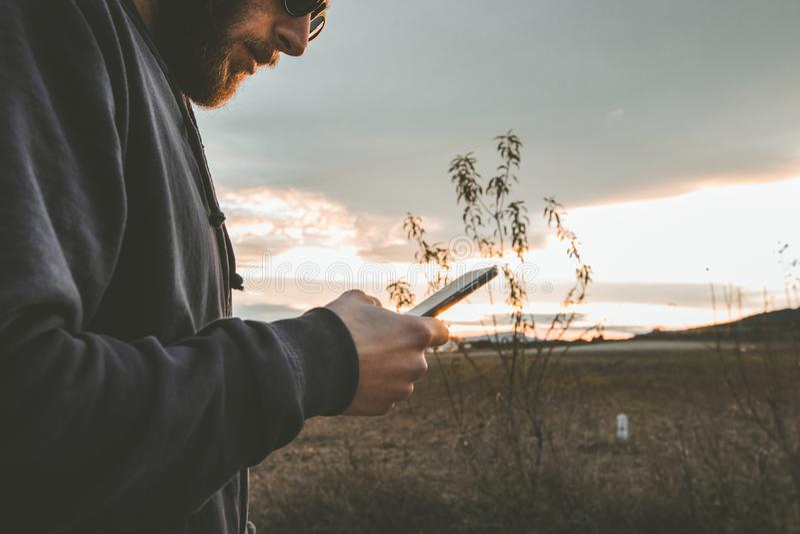 有看手机的太阳镜和盖帽的人 观看手机的人们 库存照片