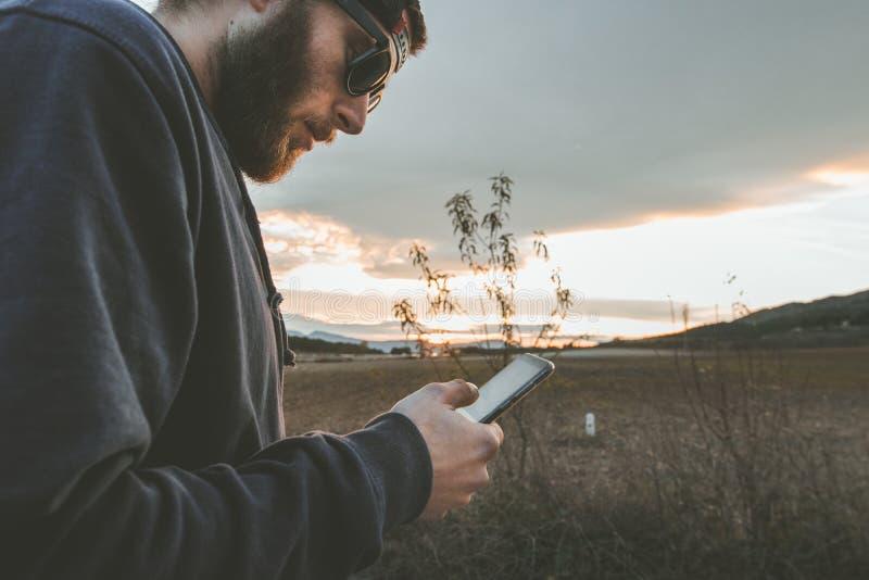 有看手机的太阳镜和盖帽的人 观看手机的人们 免版税库存照片