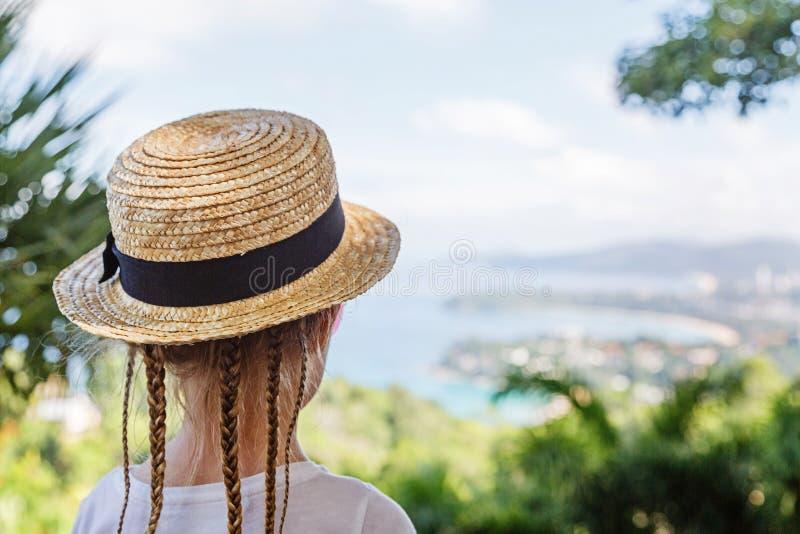 有看海的头发辫子和草帽的女孩,当站立在与优美的风景时的观点 免版税库存照片