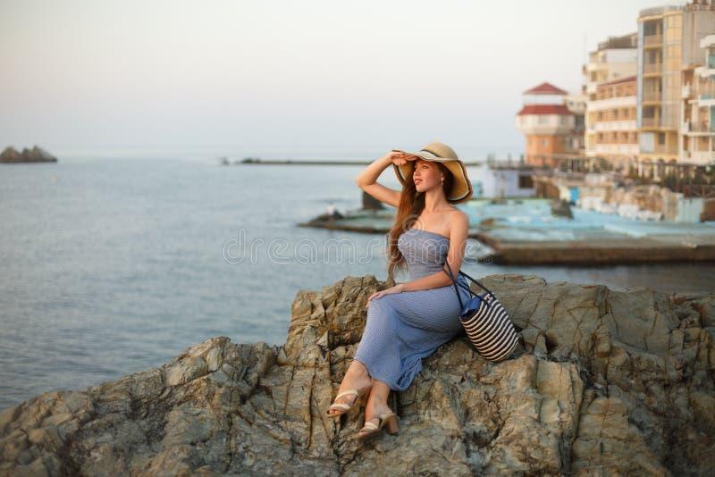 有看海的白色草帽的可爱的美丽的妇女和日落或者日出 有夏天海滩的女性 免版税库存图片