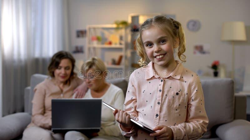 有看照相机、妈妈和老婆婆的片剂的女孩使用膝上型计算机,现代家庭 库存照片