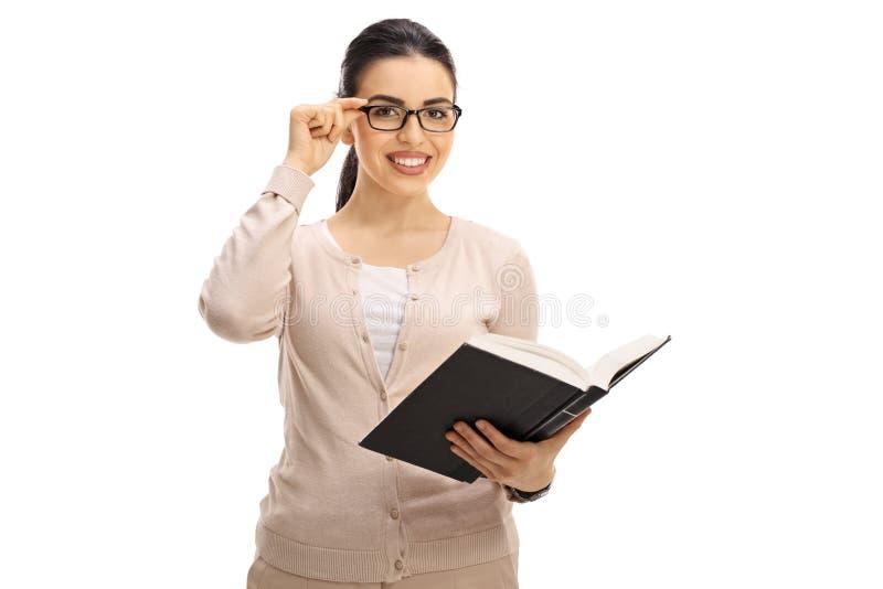 有看照相机和微笑的书的女老师 库存照片