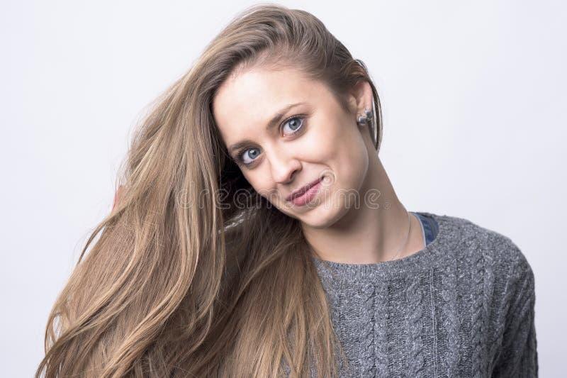 有看照相机和微笑的长的健康棕色头发的年轻调情的妇女 免版税图库摄影