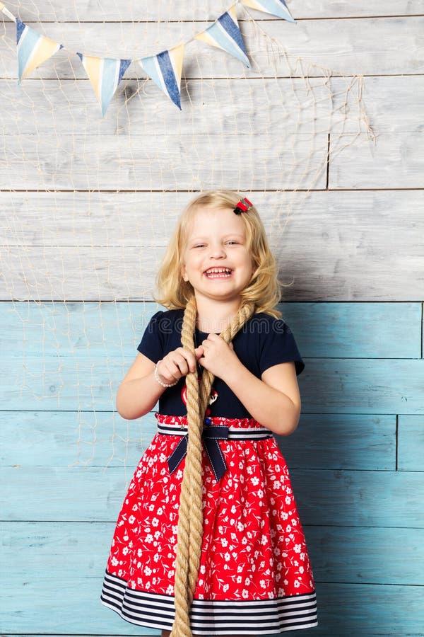 有看照相机和笑的绳索的小女孩 库存图片