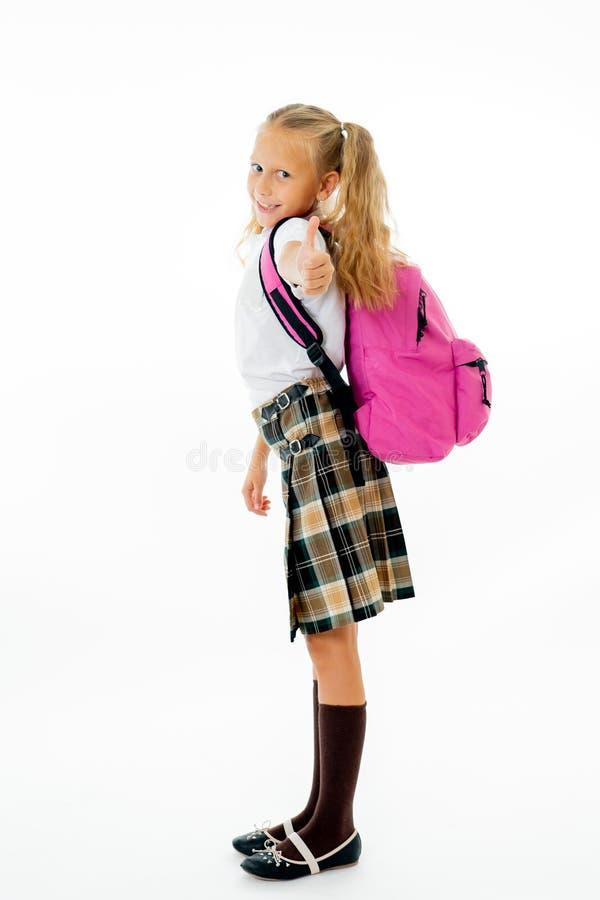 有看照相机的一个桃红色书包的俏丽的逗人喜爱的金发女孩显示愉快赞许的姿态去教育隔绝  免版税库存照片