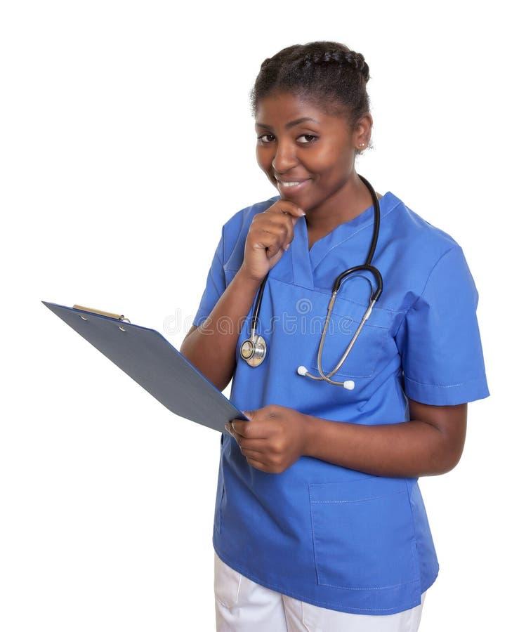 有看照相机的剪贴板的非洲护士 库存照片