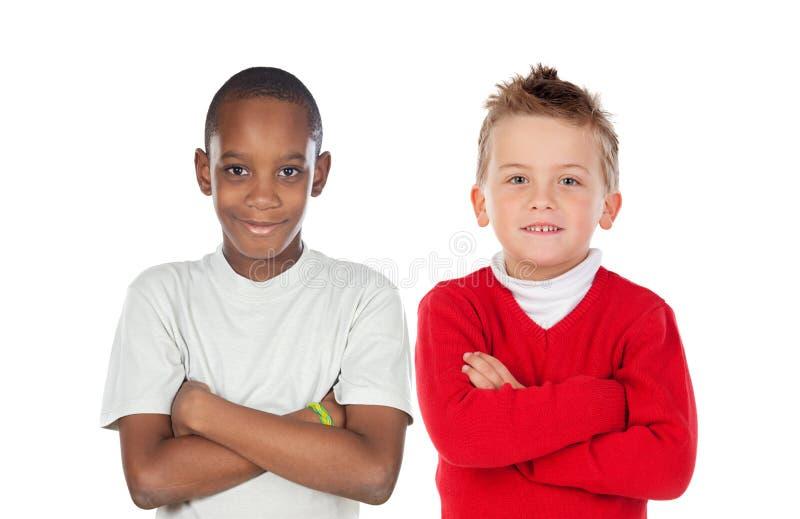 有看照相机的横渡的胳膊的两differents孩子 库存照片