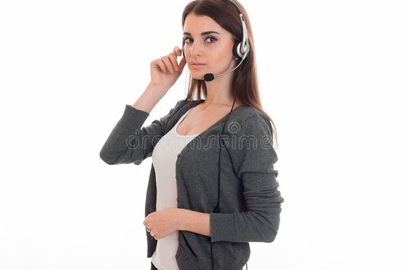 有看照相机的耳机和话筒的年轻俏丽的深色的女商人隔绝在白色背景 库存照片