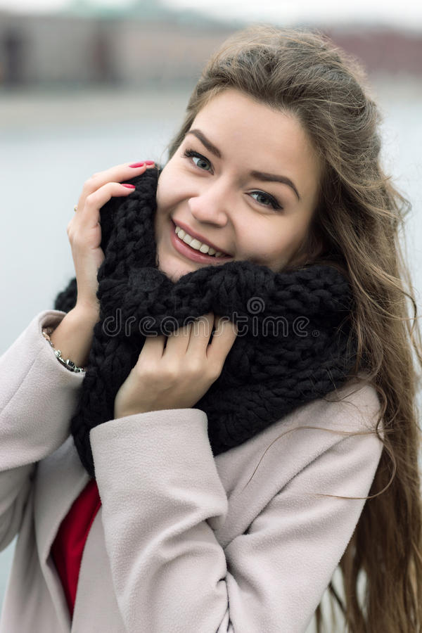 有看照相机的自然构成的微笑的女孩 一件黑外套、一条围巾和一件红色礼服的女孩反对灰色天空 不是我 免版税库存图片