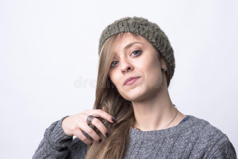 有看照相机的被编织的灰色盖帽掠过的头发的确信的质朴的行家女孩 库存照片