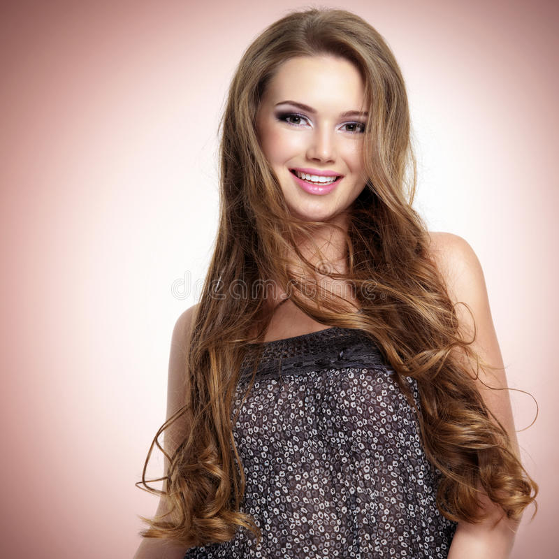 有看照相机的长的头发的美丽的年轻微笑的妇女 免版税库存图片