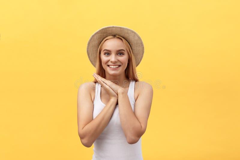 有看照相机,在黄色背景的愉快的退出的情感面孔的年轻迷人的白肤金发的妇女 免版税图库摄影