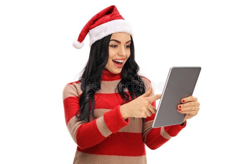 有看片剂的圣诞节帽子的快乐的妇女 免版税库存图片