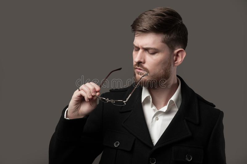 有看玻璃的胡子的想法的时髦的人 免版税库存图片