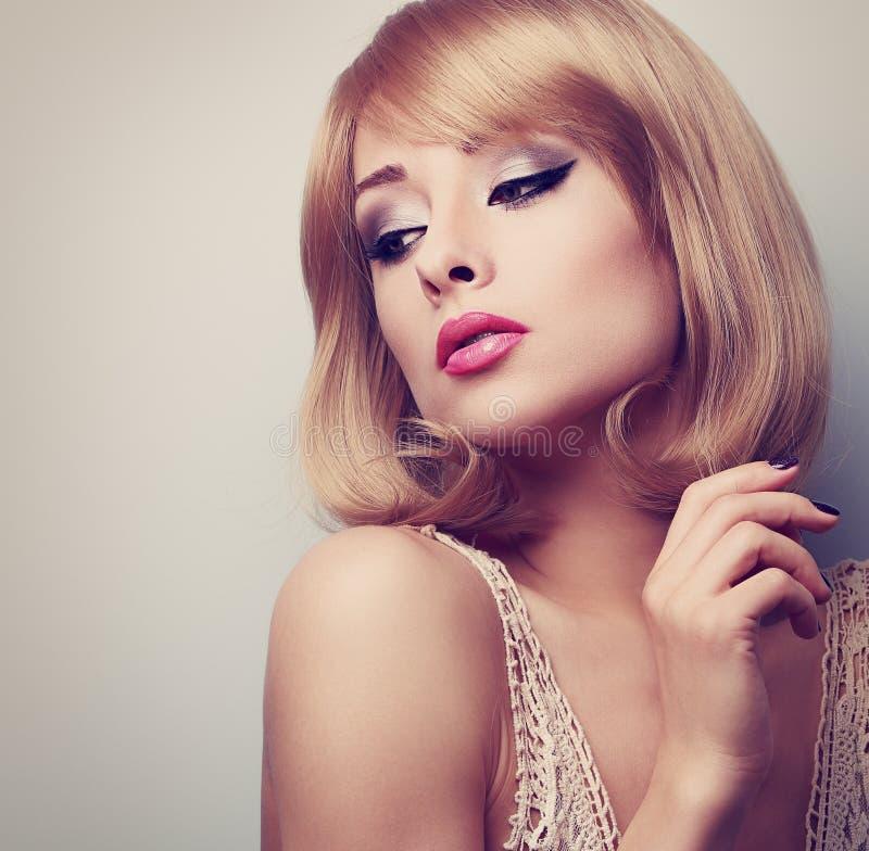 有看短发的样式的美丽的白肤金发的构成妇女下来 库存图片