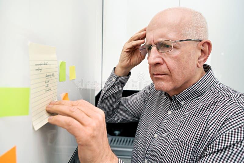 有看笔记的老年痴呆的年长人 免版税库存图片