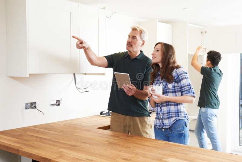 有看计划的木匠的妇女为数字式选项的厨房 库存照片