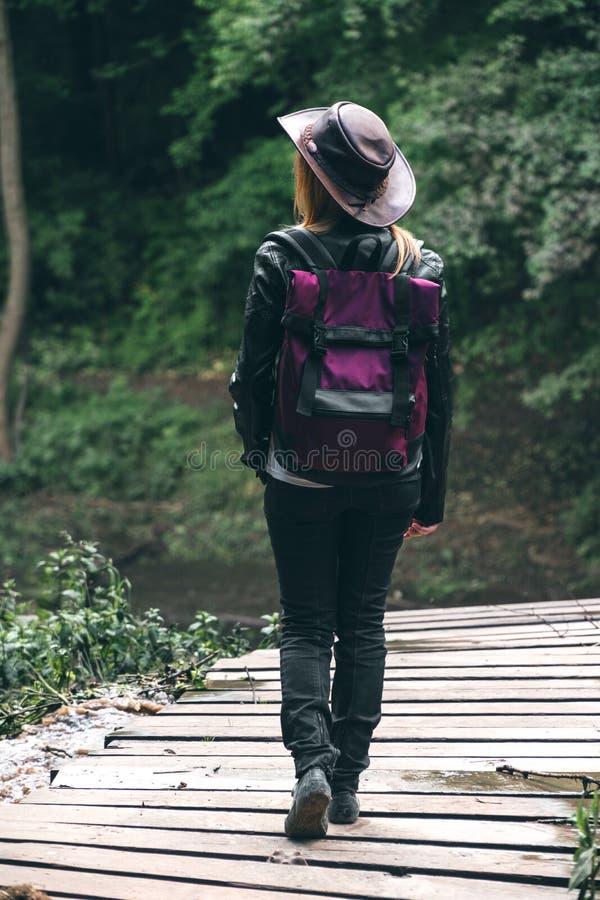 有看距离的一个桃红色背包和皮革牛仔样式帽子的年轻女性游人 ?? 冒险概念, 图库摄影