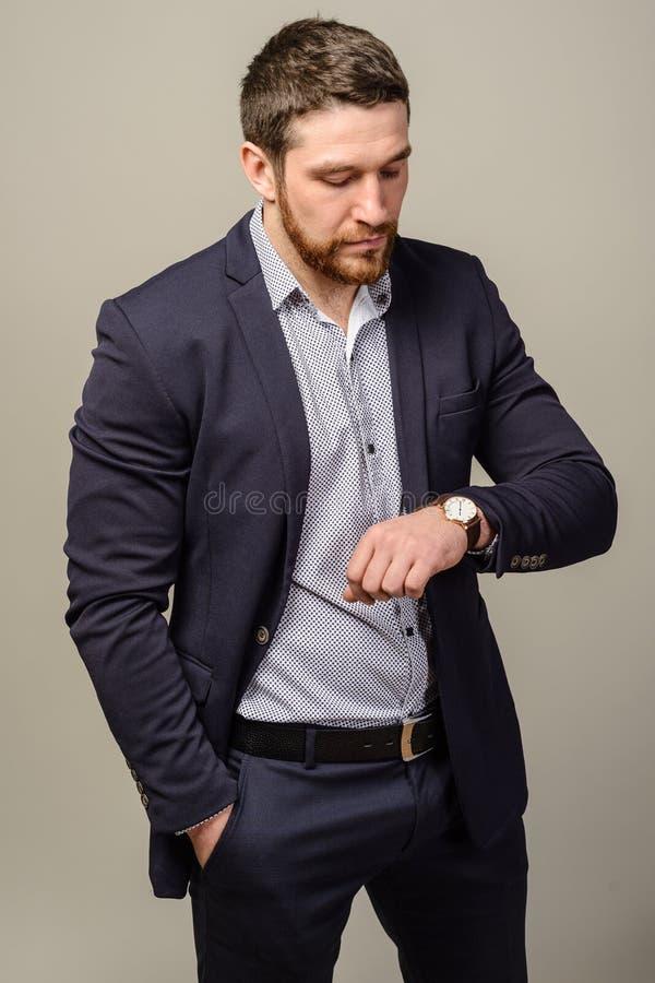 有看他的手表的胡子的英俊的穿着体面的人 免版税库存照片