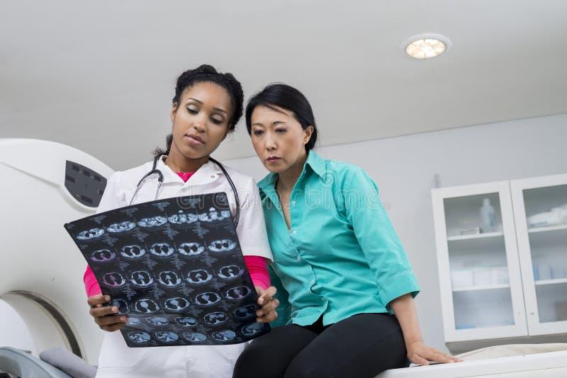 有看CT扫描胸部X光的放射学家的被拉紧的妇女 库存照片