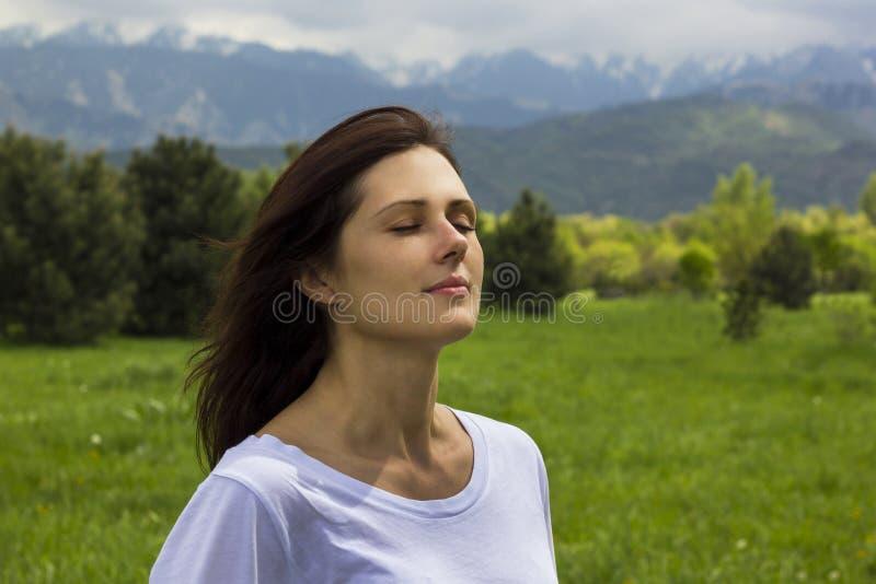有眼睛的少妇关闭了在山的呼吸的新鲜空气 免版税库存照片