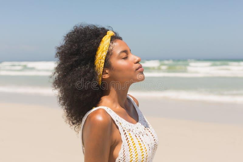 有眼睛的年轻非裔美国人的妇女结束了站立在海滩 库存图片