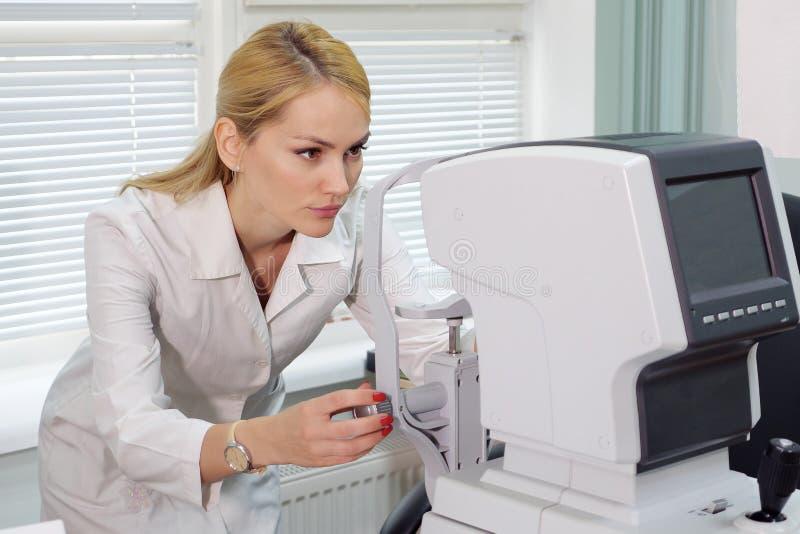 有眼科设备的眼科医生妇女在内阁 库存照片