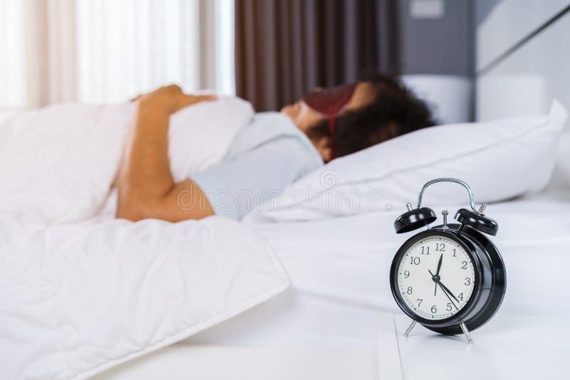 有眼罩的资深妇女睡觉在床上的 免版税库存照片