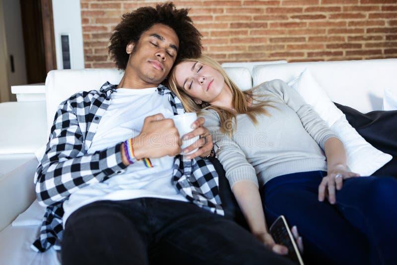 有睡着的,当在长沙发的看着电视在家时的放松的年轻夫妇 免版税库存照片