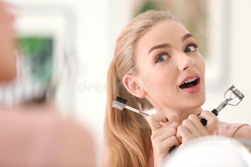 有睫毛卷发的人和梳子的情感少妇 库存照片