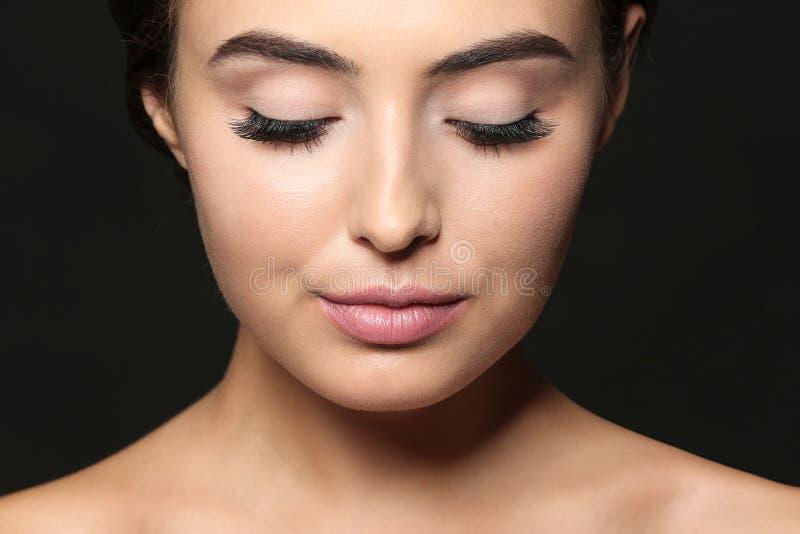 有睫毛引伸的美丽的少妇在黑暗的背景 免版税库存图片