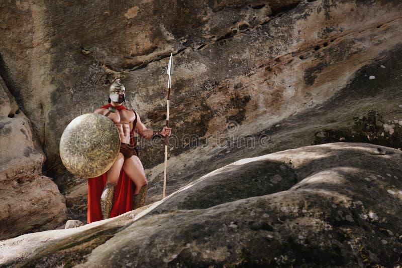有矛的争论者在岩石 免版税图库摄影