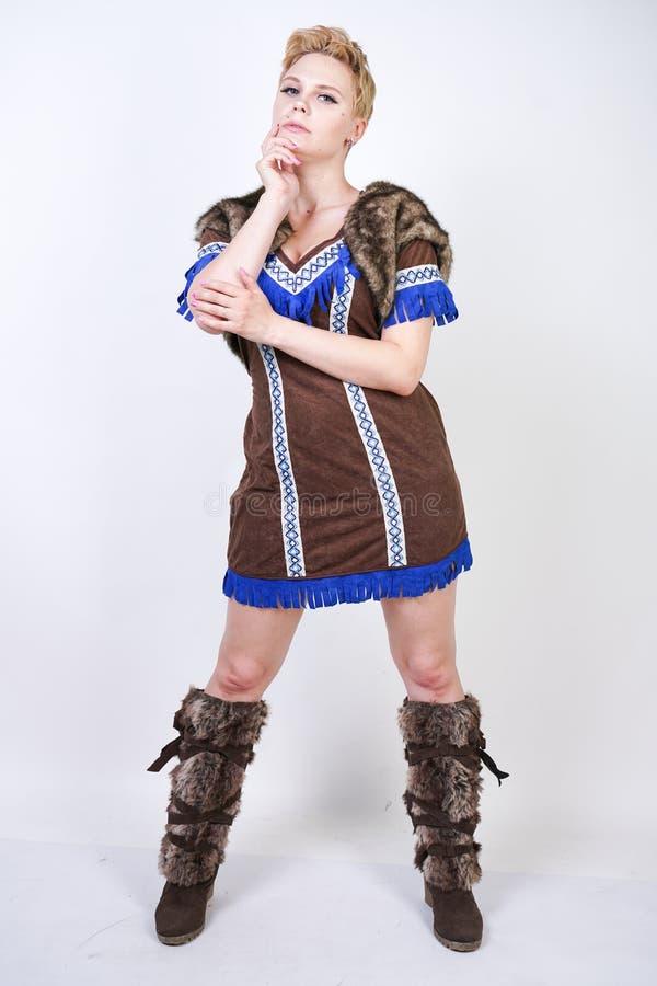 有短发和正大小形象的坚强的妇女在有情感地积极地摆在的轴的原始猎人服装在白色ba 库存照片