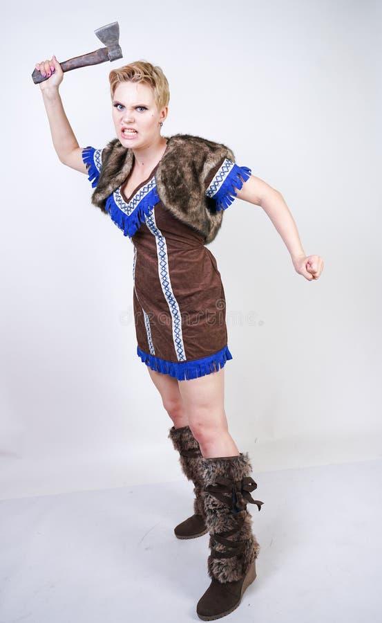 有短发和正大小形象的坚强的妇女在有情感地积极地摆在的轴的原始猎人服装在白色ba 库存图片