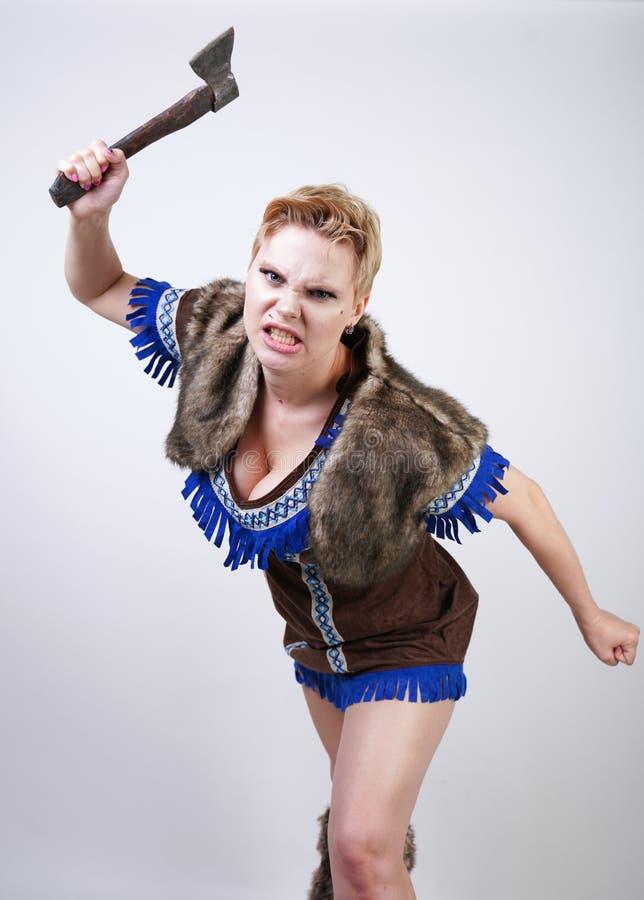 有短发和正大小形象的坚强的妇女在有情感地积极地摆在的轴的原始猎人服装在白色ba 免版税图库摄影