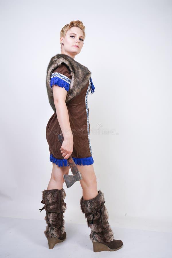 有短发和正大小形象的坚强的妇女在有情感地积极地摆在的轴的原始猎人服装在白色ba 免版税库存照片